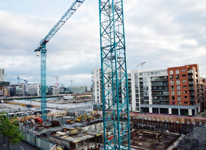 A construction site in Dublin's docklands with a view of the city and multiple cranes dotting the skyline.