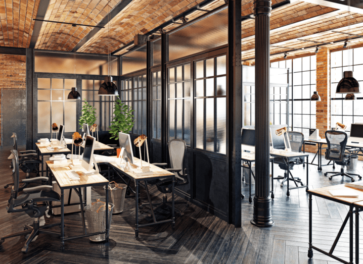 A modern, bright office space, with exposed brick walls, plants and decorative lights.
