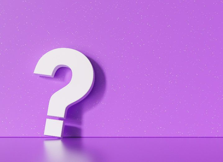 Rendering of a large, three-dimensional white question mark leaning against a speckled purple wall.