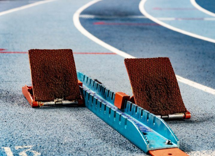 Athletics starting blocks with orange foot pads on a blue race track.