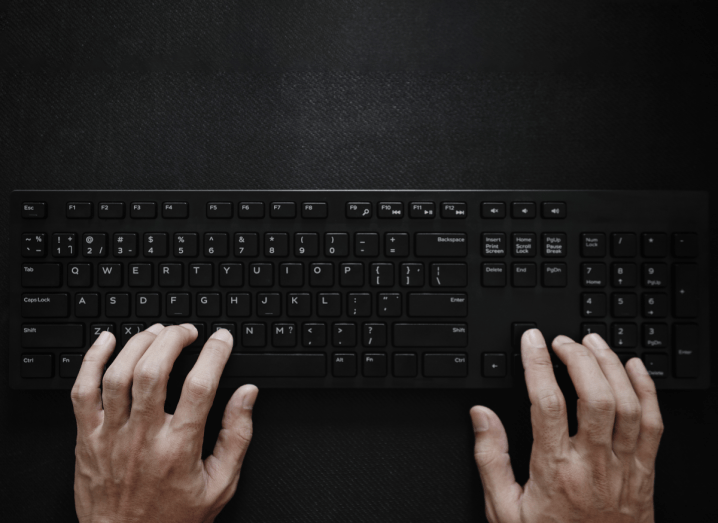 Two hands typing on a black computer keyboard over a black background.