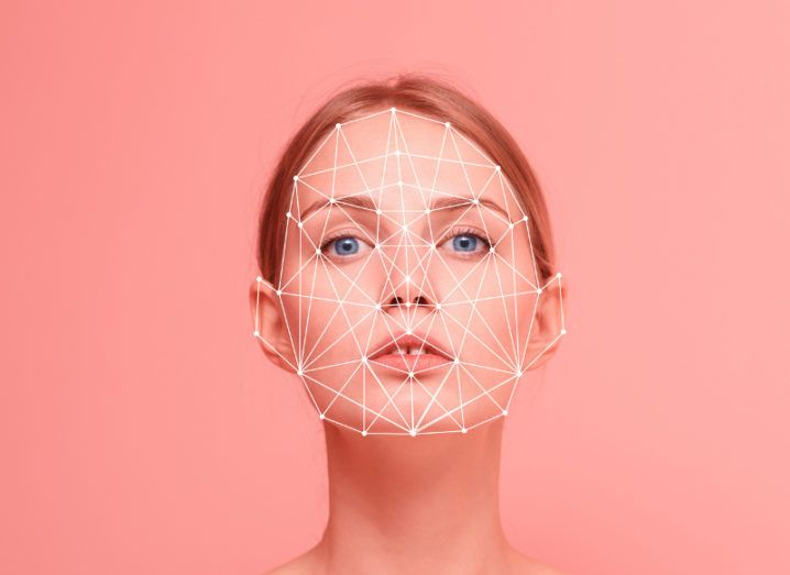 View of woman with pulled back red hair looking at camera with face covered in digital lines to represent facial recognition.