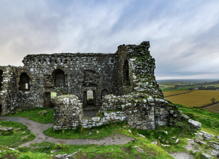 A crumbling castle covered in moss, raised on a hill over the countryside of Laois. The sky behind it is cloudy.