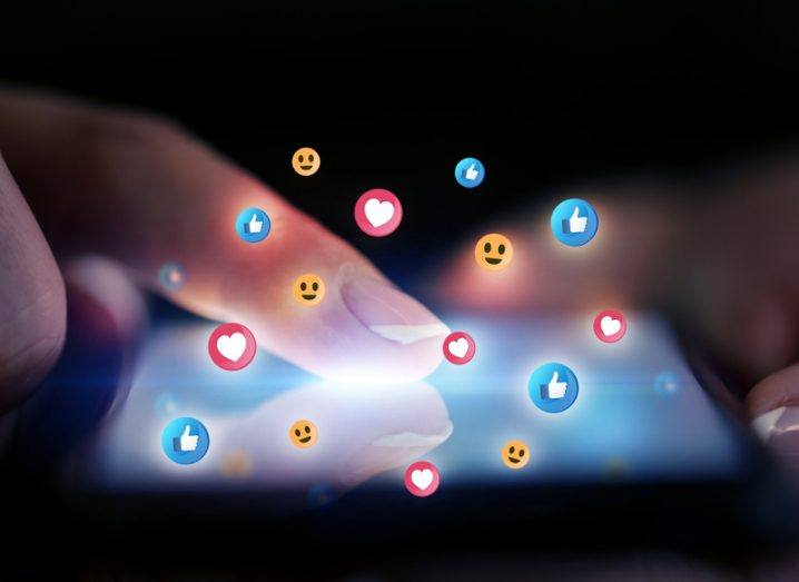 Darkly lit close-up of fingers scrolling on a smartphone screen with smiling emojis, hearts and thumbs-up icons floating out of the screen.