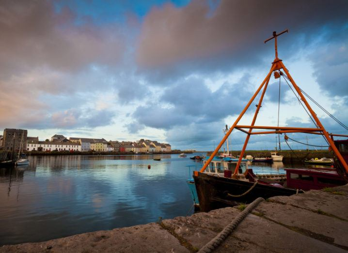 A view from the harbour of Galway city at sunset, with a boat in the foreground and the city's colourful skyline in the background.