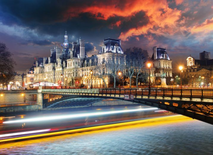 A bridge crossing a river in Paris, leading to a large, decorative building dating back centuries, lit up at night.
