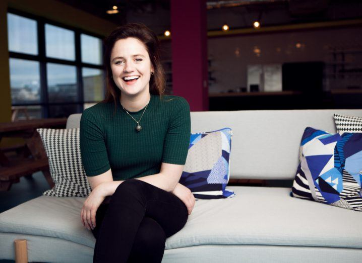 A young woman with dark hair and a green top sits on a sofa with blue cushions in a modern Huckletree office space.