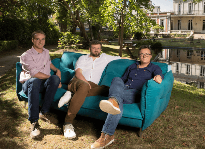 Three men sit on a blue sofa in a garden beside a pond. One man is wearing a pink shirt and dark blue jeans, sitting beside a man in chinos and a white shirt, and another man in a dark denim shirt and light blue jeans.