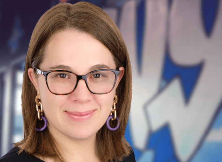A woman with black glasses and brown hair smiles into the camera, in front of a background wall with graffiti on it. She is wearing purple hoop earrings.