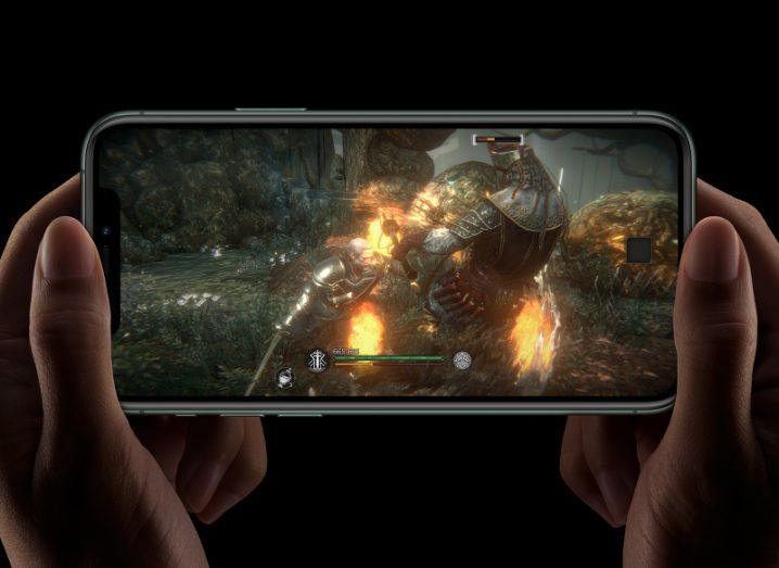Two hands hold up an iPhone 11 device while playing a video game.