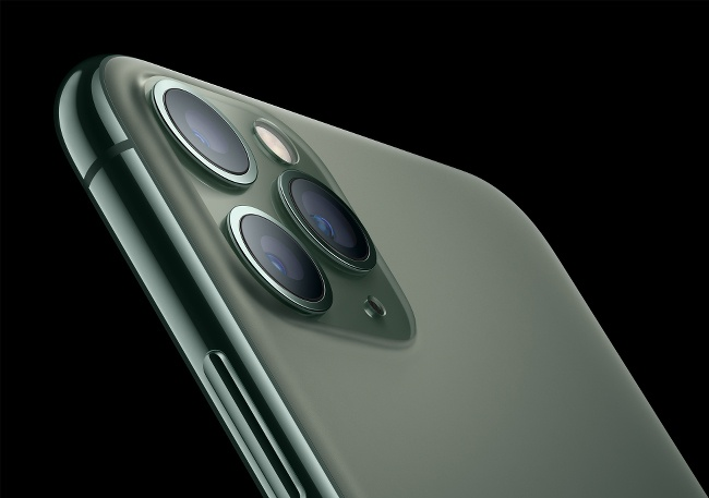 A close-up of a rear corner of an iPhone 11 handset showing a three-camera array.