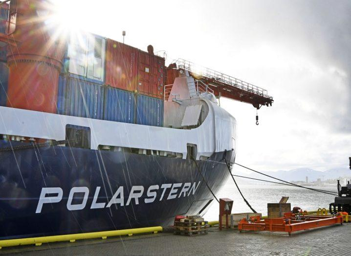Side view of the Polarstern research ship at port with the sun overhead.