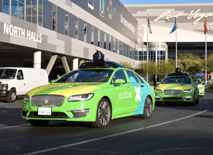A green AutoX autonomous taxi outside a large grey building in Las Vegas.