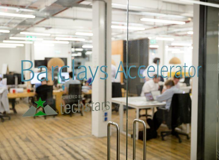 A clear glass door looking into an office space where workers are sitting at their desks. On the door it says Barclays Accelerator.