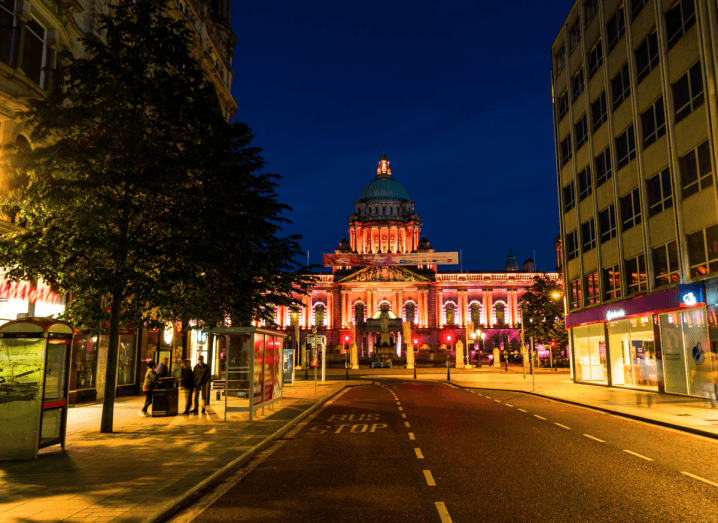 A nighttime photograph of Belfast City Hall at the top of a street in the city, which is lined with trees and phone booths. There's a red light shining on Belfast City Hall.