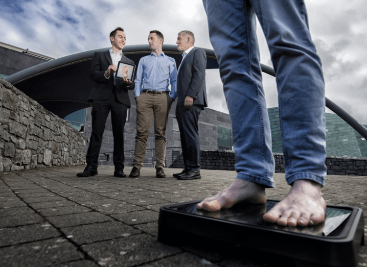 A person in blue skinny jeans stands on the Bluedrop Medical device while three men in the background hold a framed photo of a foot. They are all outdoors, in front of a tall grey building and a wall made of stone.