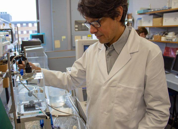 Dr Vassilis Sboros wearing a white lab coat and glasses working with equipment in his lab.
