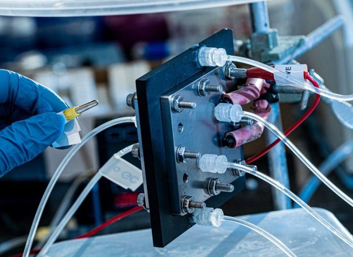Close-up of an electrocatalysis reactor with wires connected and a hand with glove to the left of the shot.
