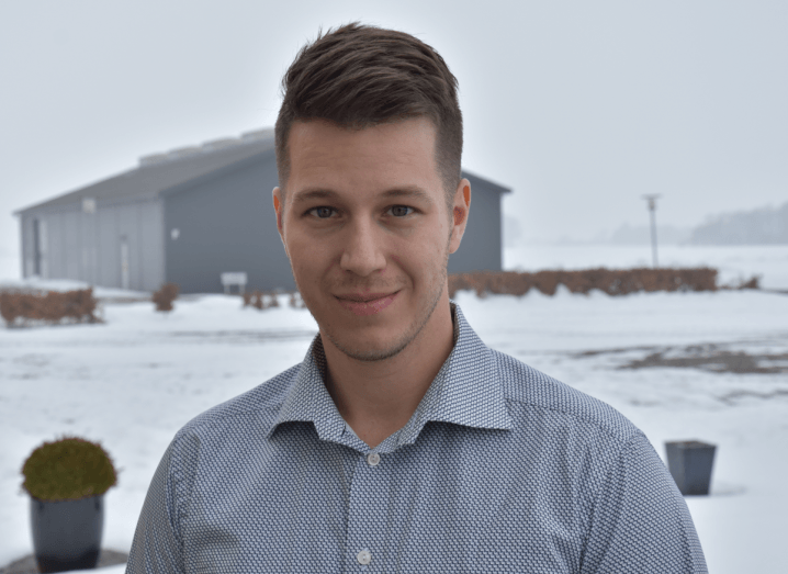 Cellevate's CEO stands in front of a snow-covered ground and a grey warehouse, wearing a grey shirt with the top button undone. He has light brown hair and is smiling into the camera.