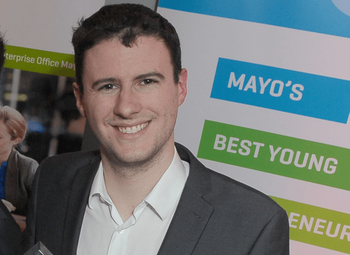 "Daniel Loftus smiles into the camera, wearing a grey suit and white shirt. He is standing in front of a sign that says ""Mayo's Best Young Entrepreneur""."