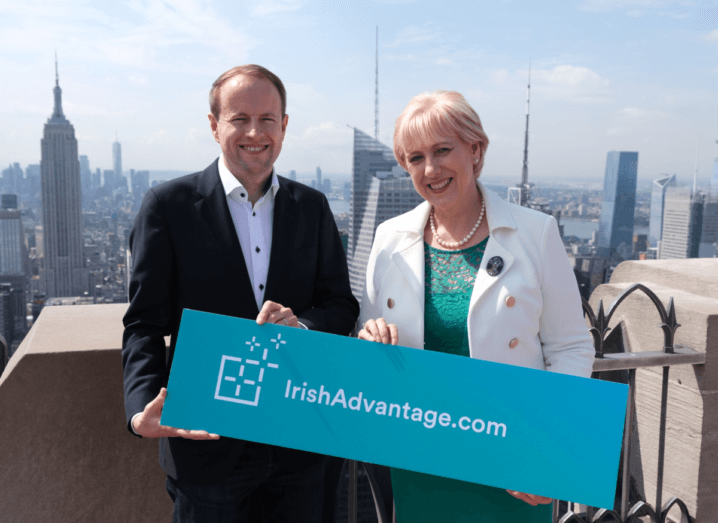 A man in a black suit and white shirt stands on top of the Rockefeller building with a woman in a green dress and a white jacket, holding a blue sign that reads Irish Advantage.