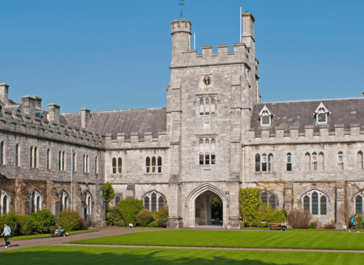 A grey, castle-like building sits in front of a neat grass lawn under a clear blue sky.