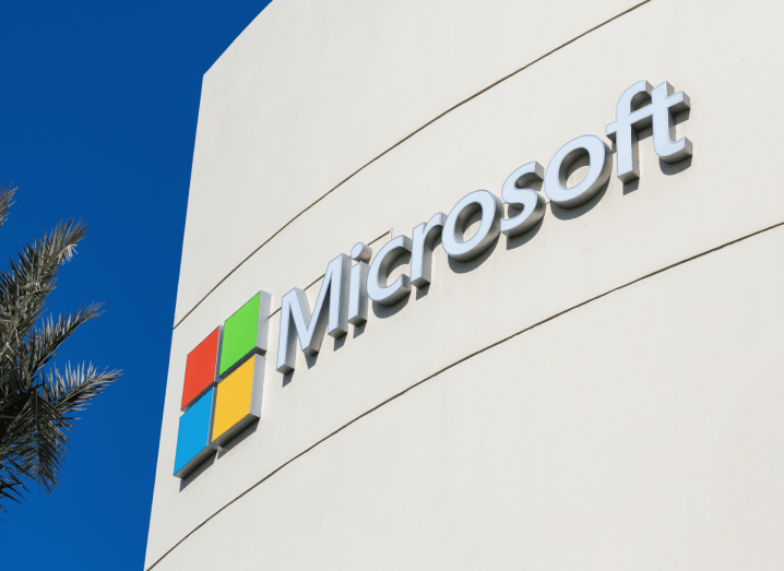 A tall white building with Microsoft's logo on the front of it, beside a palm tree and a blue sky.