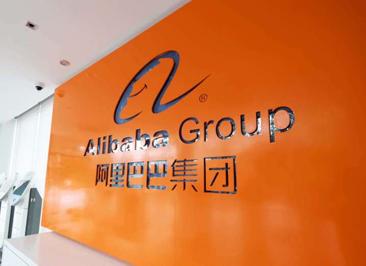 An orange wall in a bright room that reads 'Alibaba Group'.