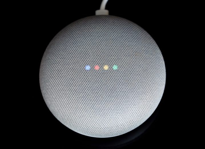 Overhead view of a small round speaker with four faint lights in blue, red, yellow and green on its surface.