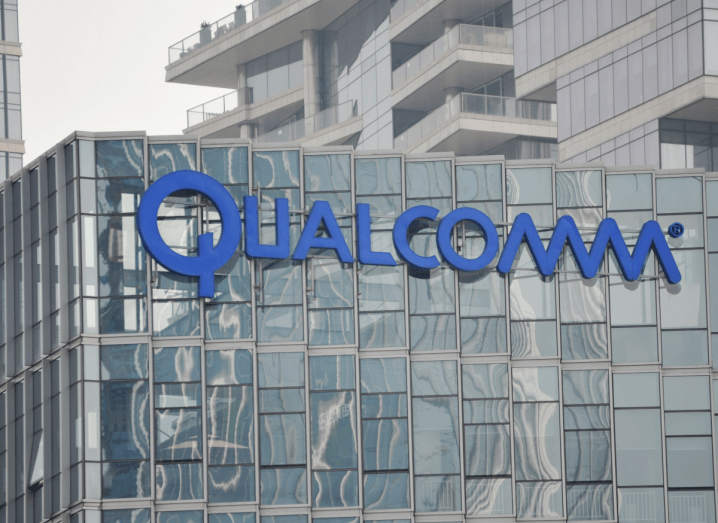 A glass building with the blue Qualcomm logo on the side of it.