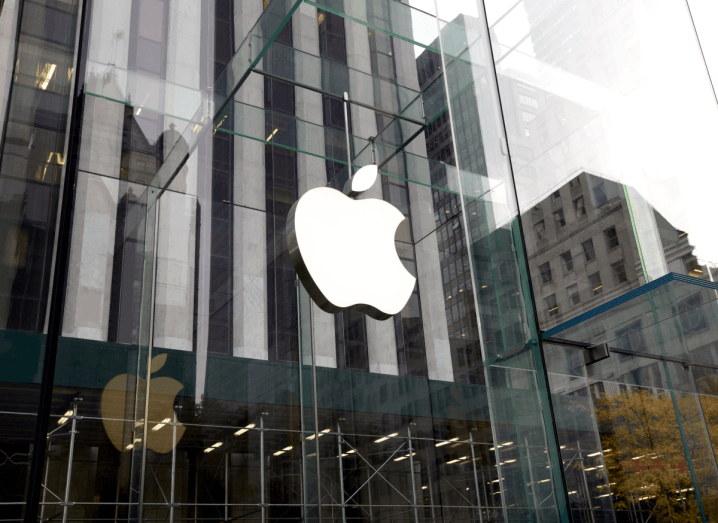 A glass building with the Apple logo on the outside.
