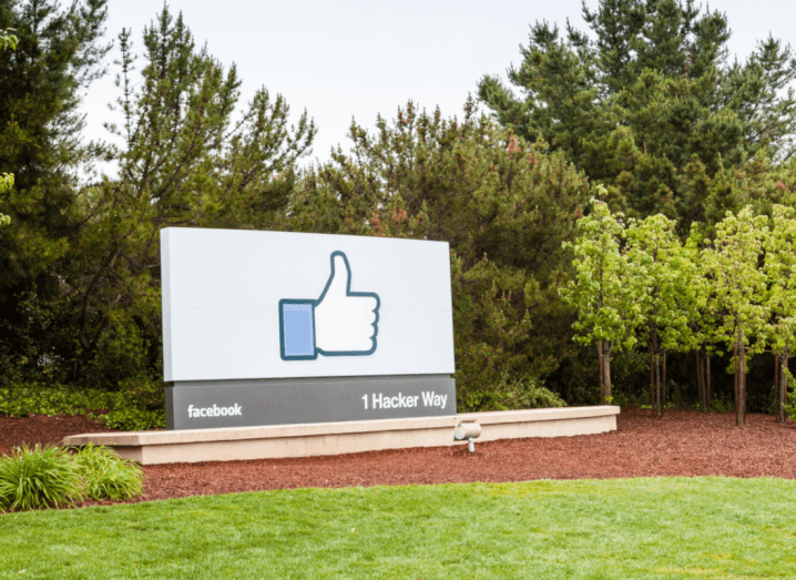 The Facebook thumbs-up logo on a sign in a patch of grass. There are trees behind it.