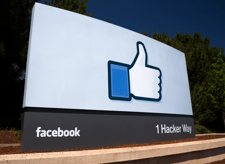"A white sign with Facebook's thumbs up logo on it that reads ""Facebook, 1 Hacker Way"", to mark the company's address in Silicon Valley. The sign is in front of trees and a clear blue sky."
