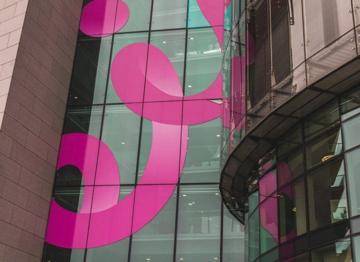 Pink Eir logo on the side of a glass building.