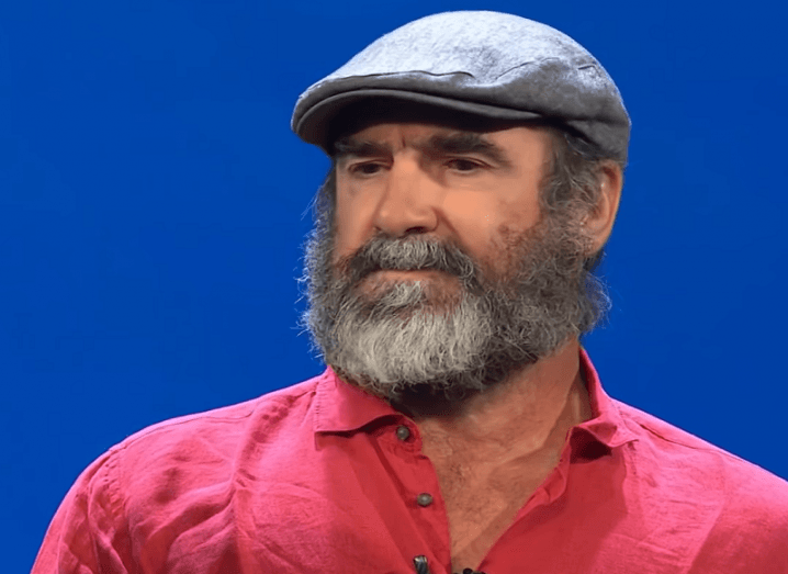 Eric Cantona in a red shirt and grey flat cap against a blue background.