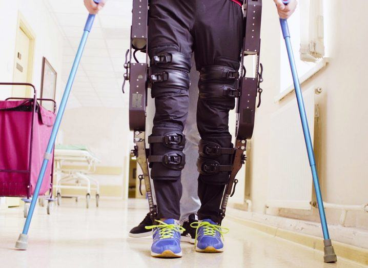 Person wearing an exoskeleton using crutches to walk down a hallway.