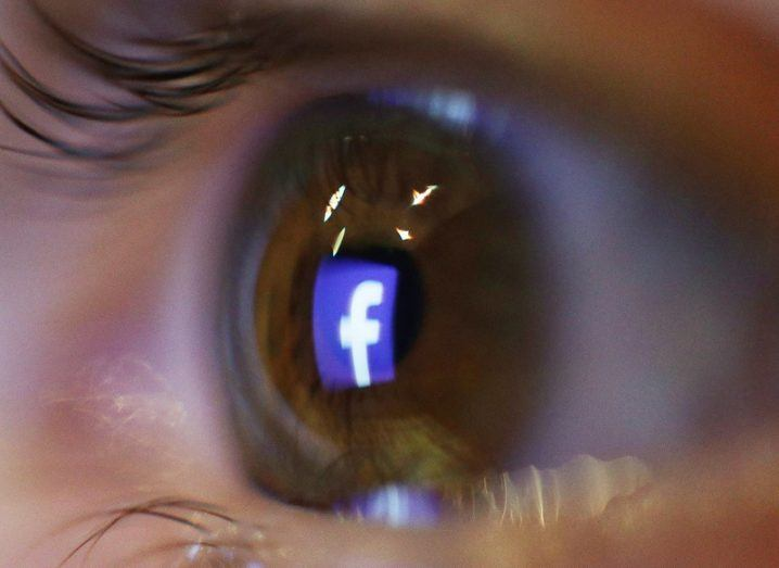 Close-up of an eye with the Facebook logo in it.