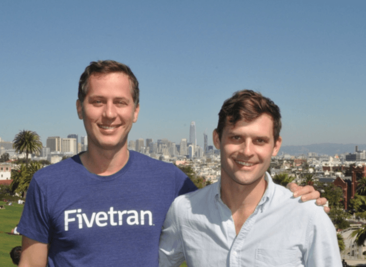 """A man in a navy-blue t-shirt that says """"Fivetran"""" stands beside a shorter man in a white shirt. They both have brown hair and are smiling. They are standing on a hill in front of the San Francisco skyline on a sunny day."""