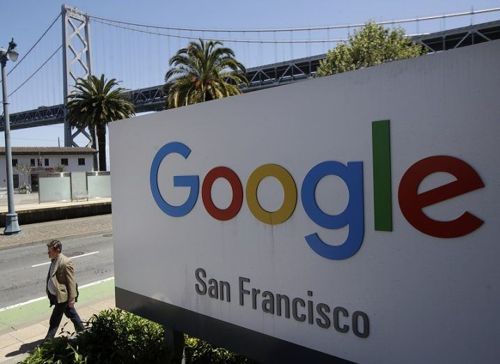 A person walks past a Google sign outside with a span of the San Francisco Bay Bridge in the background.