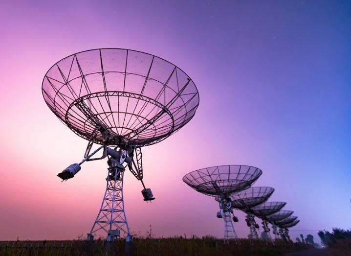 Series of radio telescopes against a purple and pink sky.