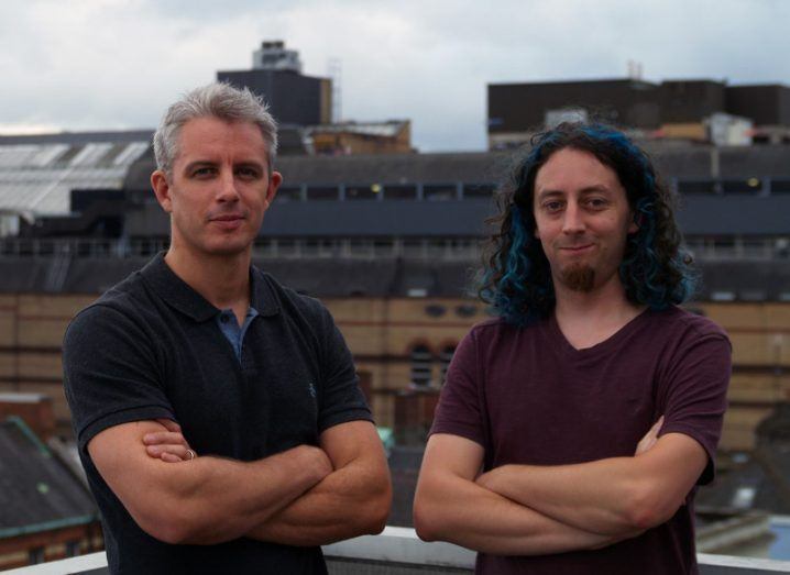 A man with grey hair stands with his arms crossed in a black t-shirt beside another man with long, black hair and blue streaks, who is wearing a burgundy t-shirt. In the background is Stephen's Green Shopping Centre's multi-story carpark against the Dublin skyline.