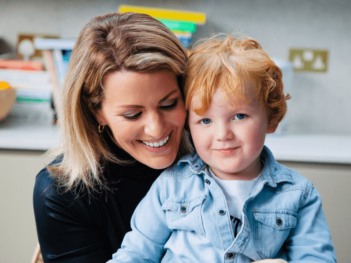 A woman with blonde hair and small gold hoop earrings wearing a black jumper hugs her son in a playroom. He has red hair and is wearing a denim shirt.