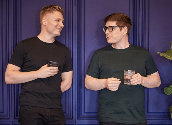 Two young men stand in front of a purple wall. The one on the left has blonde hair and is wearing a black T-shirt. The one on the right has dark hair and is wearing a green T-shirt. Both are holding glasses of water.