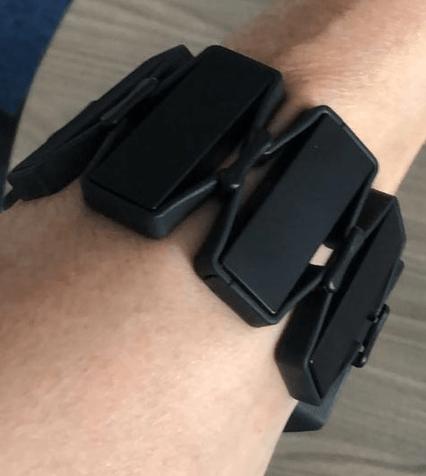 The ISL translator wristband coloured black with a number of sensors on a person's arm.