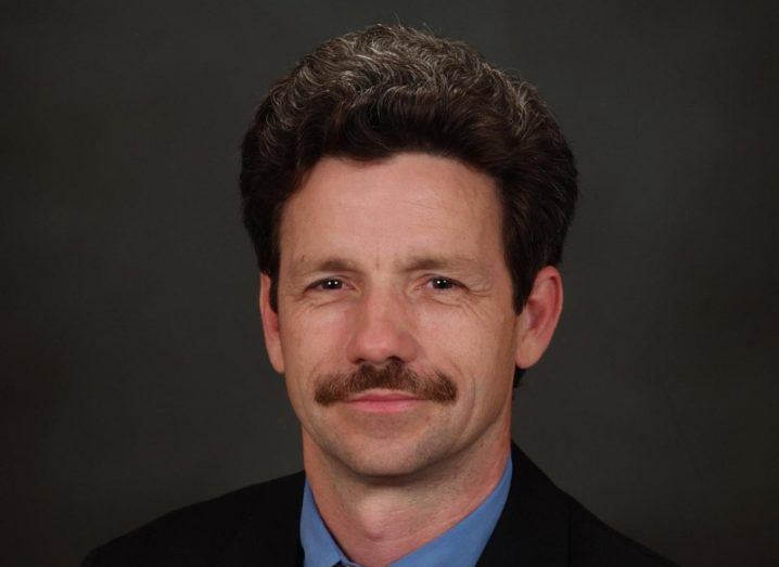 View of man with moustache and dark hair wearing blue shirt and black blazer.