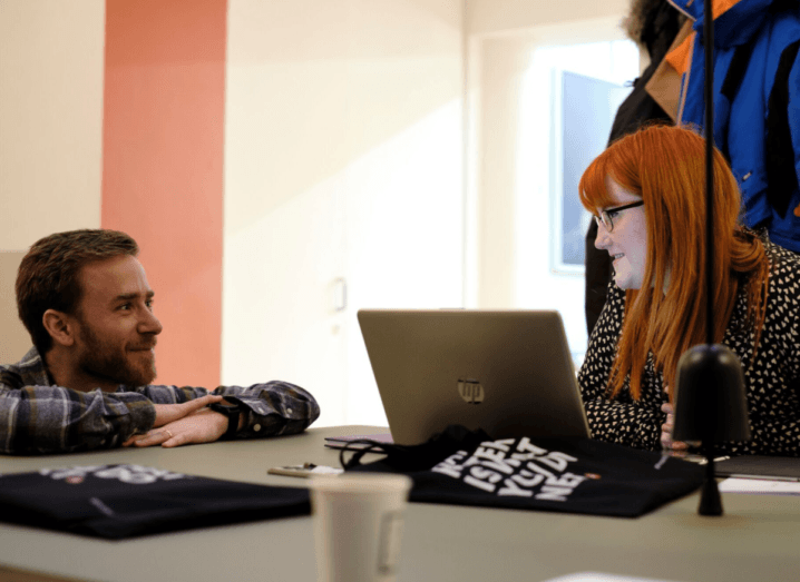 A bearded man with brown hair kneels beside a desk with his face resting on his hands, chatting with a young woman who has dyed red hair and black glasses. She is sitting in front of a HP laptop. There are coffee cups on the table.
