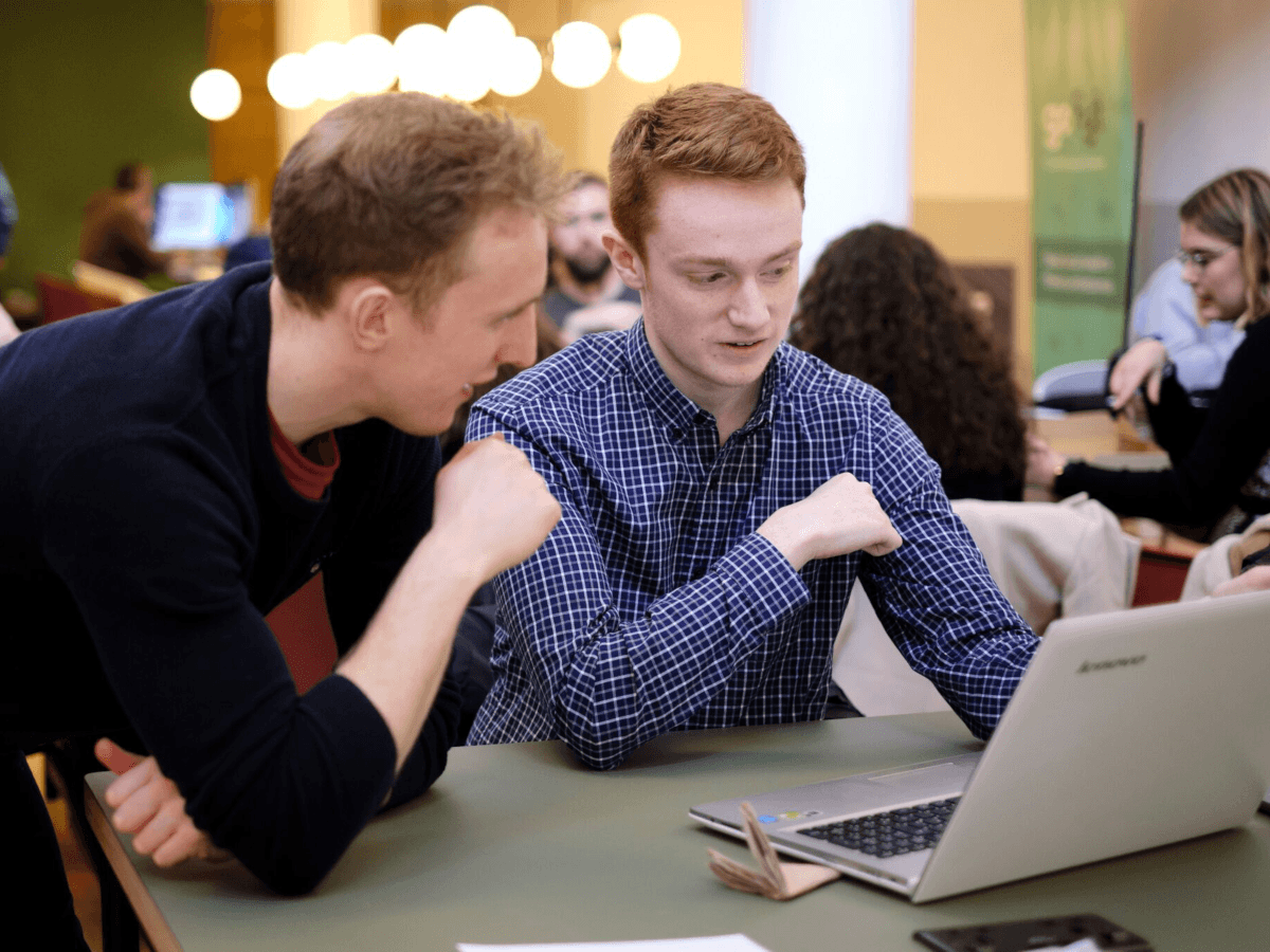 Two young blonde haired men sit beside each other and look at a laptop screen. The one on the left is wearing a black jumper while the one on the right is wearing a blue shirt.