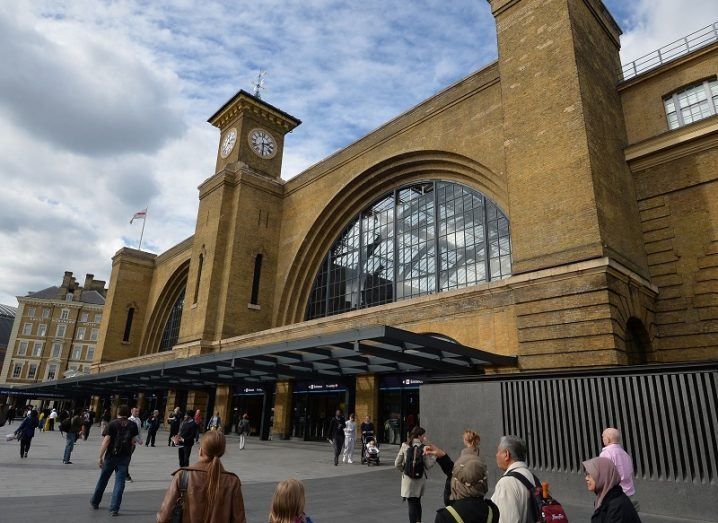 Exterior of King's Cross Station with people walking past.