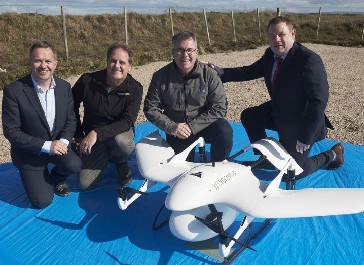 Four men smiling beside the medical delivery drone on a blue tarp.