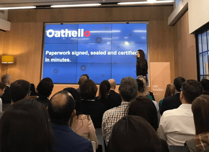 Jennifer Hourihane, a woman with long, dark hair, stands in front of a blue screen with the Oathello logo on it. She is standing in a conference room in front of an audience.